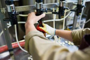 A technician does maintenance adjustments to a draft beer dispensing system