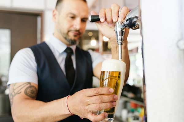 A bartender pours a draft beer from a newly installed dispensing system