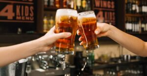Two draft beer glasses raised in two people's hands